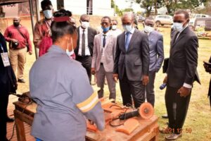 Minister Achile Bassilekin III visiting some women processing wood during the furniture fair in Yaounde